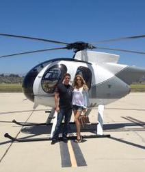 blonde standing by helicopter